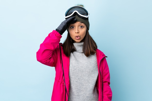 Mixed race skier girl with snowboarding glasses over isolated blue background has realized something and intending the solution