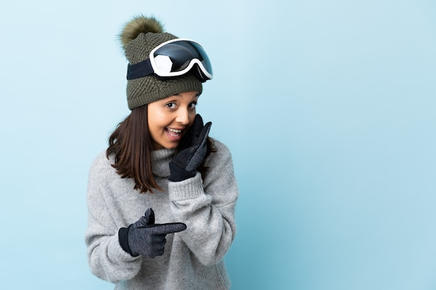 Mixed race skier girl with snowboarding glasses over isolated blue background pointing to the side to present a product and whispering something