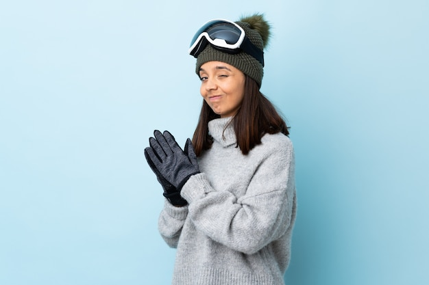 Mixed race skier girl with snowboarding glasses over isolated blue background scheming something