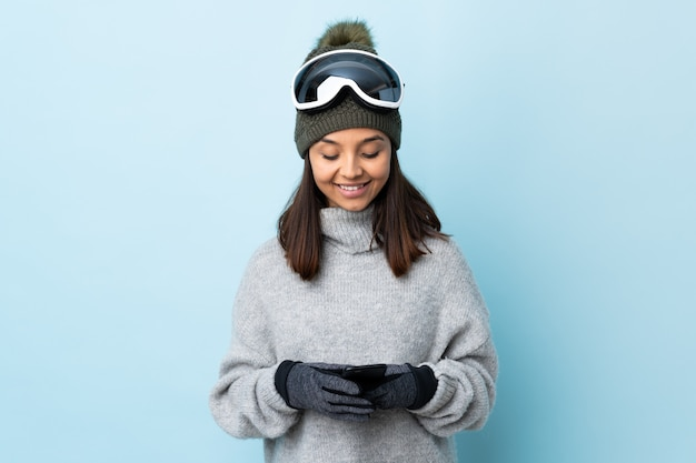 Mixed race skier girl with snowboarding glasses over isolated blue background sending a message with the mobile