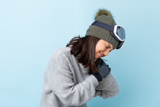Mixed race skier girl with snowboarding glasses over isolated blue background suffering from pain in shoulder for having made an effort