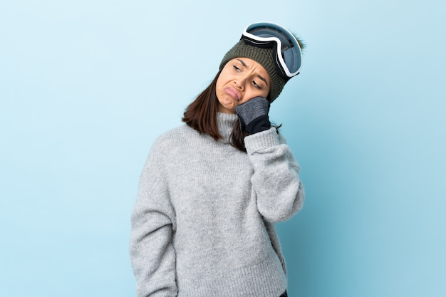 Mixed race skier girl with snowboarding glasses over isolated blue background with tired and bored expression