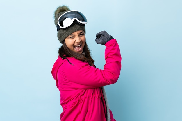 Mixed race skier girl with snowboarding glasses over isolated blue celebrating a victory.