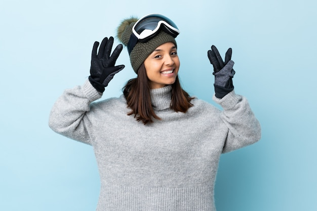 Mixed race skier girl with snowboarding glasses over isolated blue wall counting eight with fingers