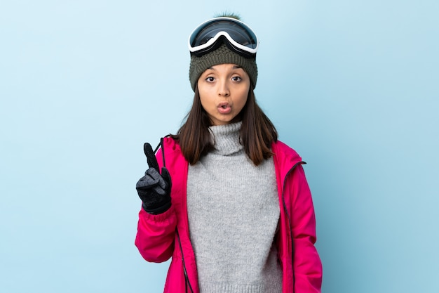Mixed race skier girl with snowboarding glasses over isolated blue wall intending to realizes the solution while lifting a finger up