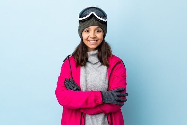 Mixed race skier girl with snowboarding glasses over isolated blue wall keeping the arms crossed in frontal position