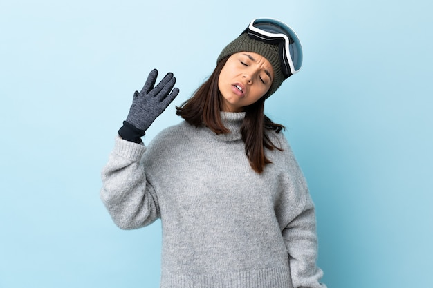 Mixed race skier girl with snowboarding glasses over isolated blue wall with tired and sick expression.