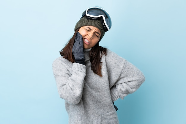 Mixed race skier girl with snowboarding glasses over isolated blue wall with toothache