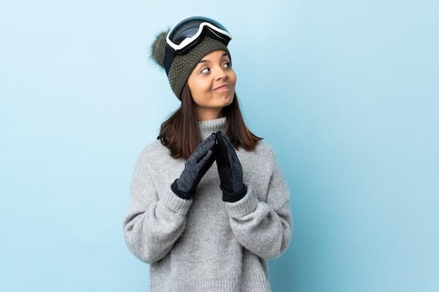 Девушка лыжника смешанной гонки с очками сноубординга на изолированном синем фоне замышляет что-то.