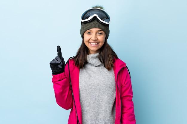 격리 된 파란색 배경 위에 스노우 보드 안경 혼혈 스키 소녀