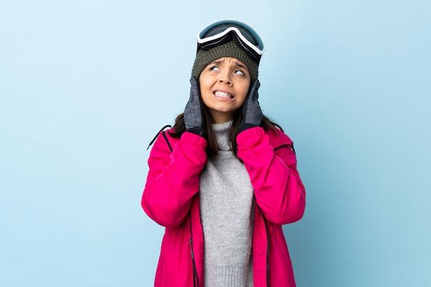 Девушка лыжника смешанной гонки с стеклами сноубординга над изолированными голубыми разочарованными и покрывая ушами.
