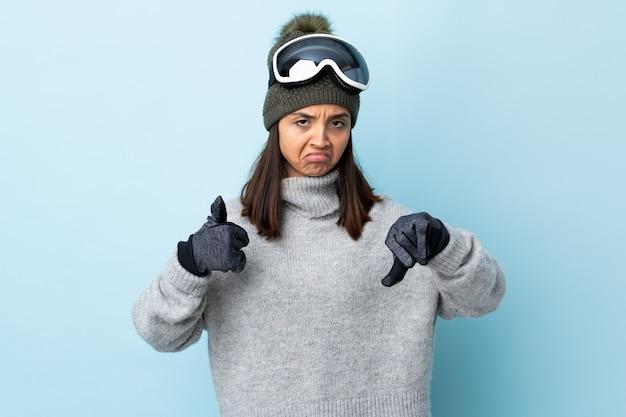 Девушка лыжника смешанной гонки с очками сноуборда над изолированной синей делая хороший плохой знак. не определился, да или нет.