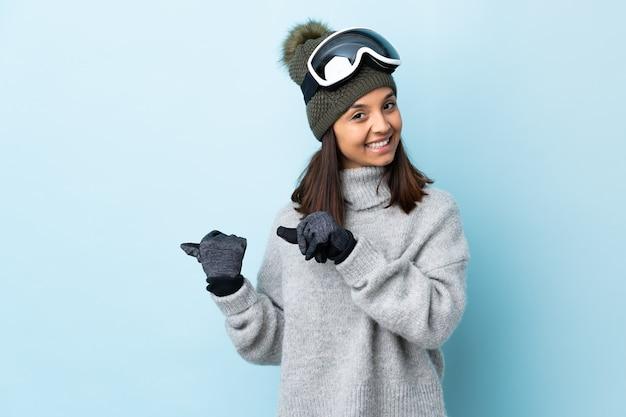 製品を提示する側を指している孤立した青の上にスノーボードグラスを持つ混血スキーヤーの女の子。
