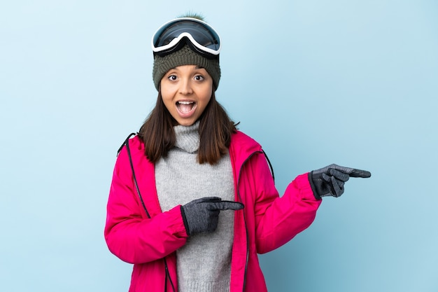 격리 된 파란색 놀과 포인팅 측면을 통해 스노우 보드 안경 혼혈 스키 소녀.