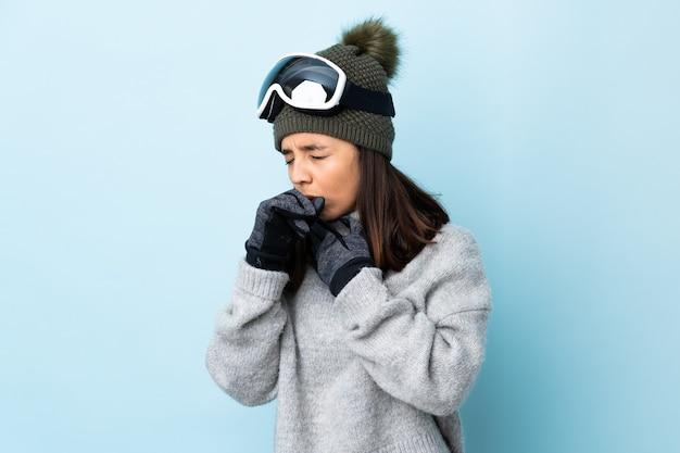 Девушка лыжника смешанной гонки с очками для катания на сноуборде над изолированной голубой стеной много кашляет.