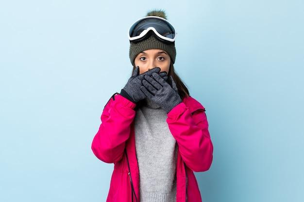 Смешанная девушка лыжника гонки с очками сноуборда над изолированной голубой стеной, покрывающей рот руками.