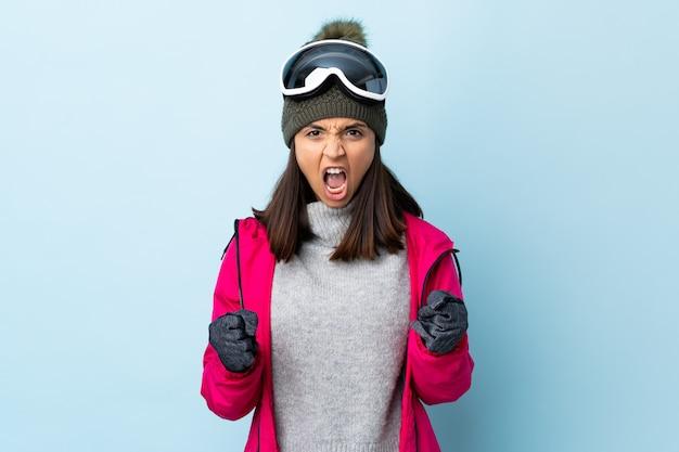 Девушка лыжника смешанной расы с сноубордическими очками на изолированной синей стене расстроена плохой ситуацией