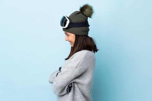横の位置で孤立した青い壁の上にスノーボードグラスと混血のスキーヤーの女の子。