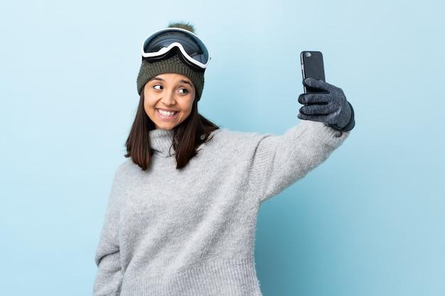 Девушка лыжника смешанной гонки с сноуборд очки над изолированных синей стеной, делая селф