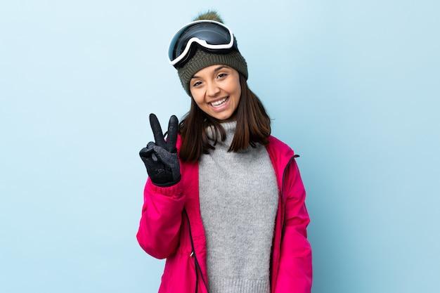 Девушка лыжника смешанной гонки с сноуборд очки над изолированных синей стеной, улыбаясь и показывая знак победы
