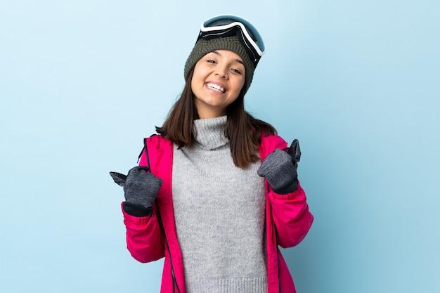 Смешанная девушка лыжника гонки с очками сноуборда над изолированной голубой стеной с большими пальцами руки вверх жестом и усмехаясь.