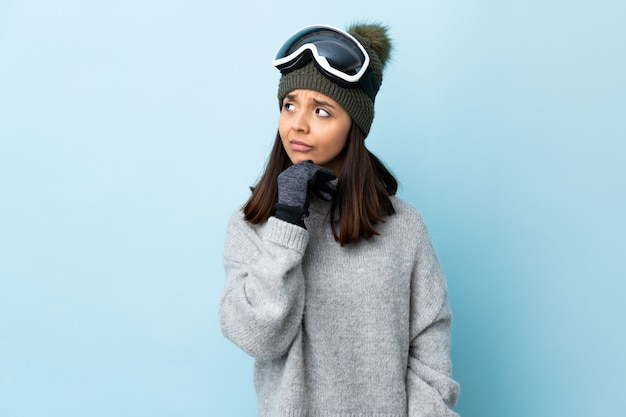 Mixed race skier woman with snowboarding glasses over isolated blue space having doubts and with confuse face expression