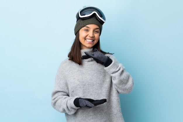 Mixed race skier woman with snowboarding glasses over isolated blue space holding copyspace imaginary on the palm to insert an ad