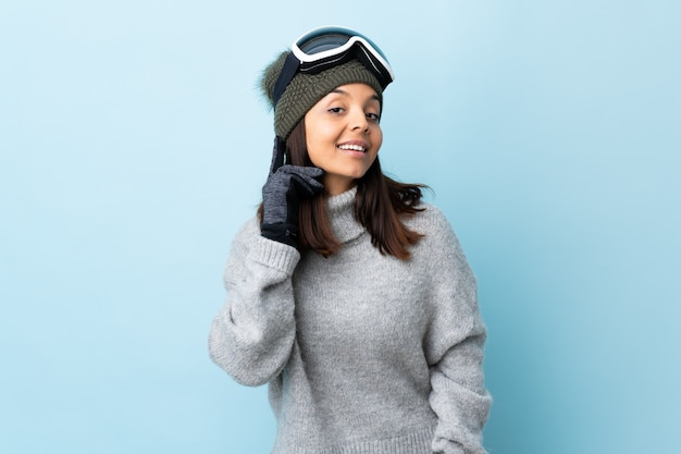 Mixed race skier woman with snowboarding glasses over isolated blue space laughing