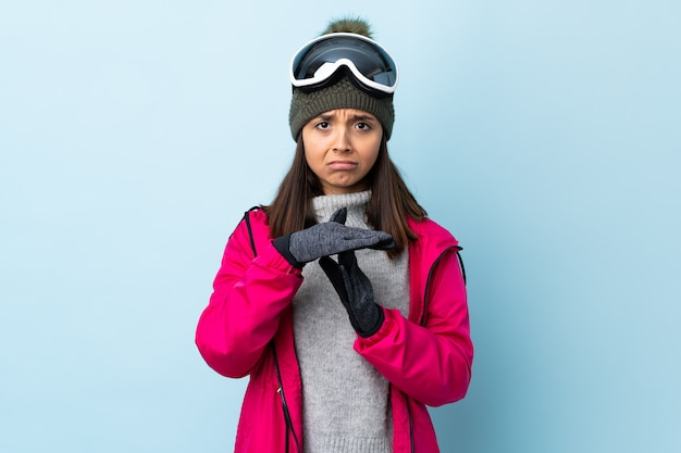 Mixed race skier woman with snowboarding glasses over isolated blue space making time out gesture
