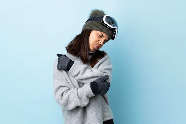 Mixed race skier woman with snowboarding glasses over isolated blue space with pain in elbow