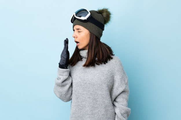 Mixed race skier woman with snowboarding glasses over isolated blue space yawning and covering wide open mouth with hand