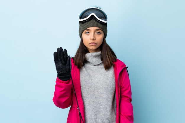 Mixed race skier woman with snowboarding glasses over isolated blue wall making stop gesture