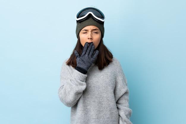 격리 된 파란색 벽 하품 및 손으로 활짝 열려 입을 덮고 스노우 보드 안경 혼합 된 경주 스키 여자