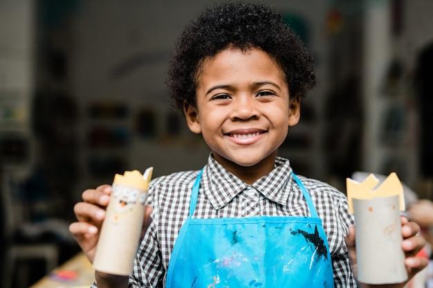 Улыбающийся школьник смешанной расы держит хэллоуинские игрушки ручной работы из свернутой бумаги на уроке в школе