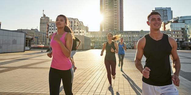 Mixed race sport team running along urban street