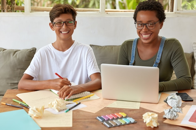 Mixed race students of high school learn together at coworking space, watch training webinar on laptop computer, write records in spiral notebook, find creative solution, have toothy smiles.