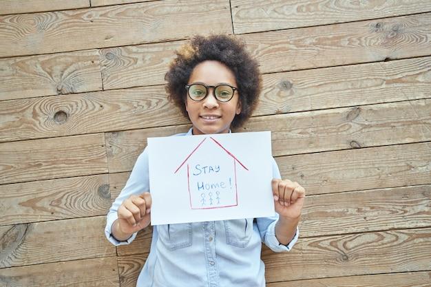 Девушка-подросток смешанной расы, держащая рисунок со словами, остается дома, стоя над деревянной стеной