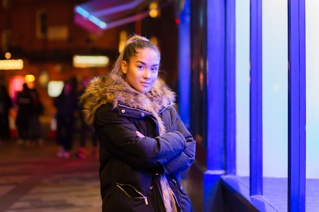 Mixed race teenage with fur coat standing next to window with blue light