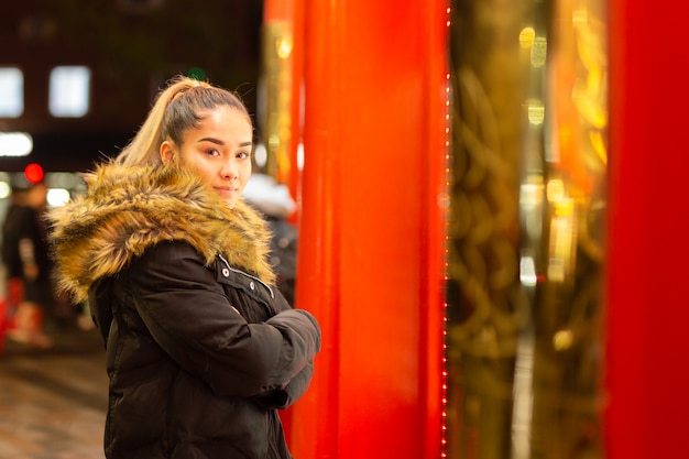 Mixed race teenage with fur coat standing next to window with red light.