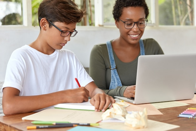 Mixed race teenagers study school course from home, do exercises