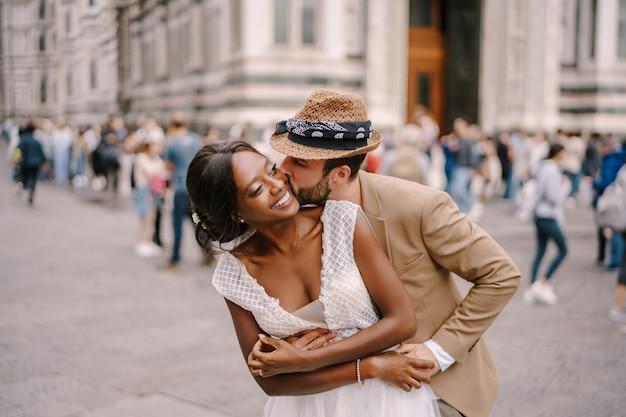 Смешанная свадебная пара. свадьба во флоренции, италия. кавказский жених обнимает сзади и целует афроамериканскую невесту.