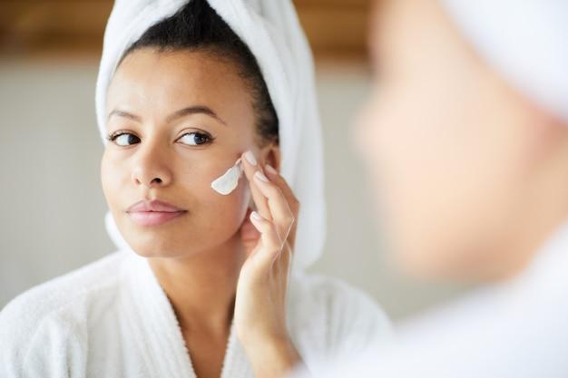 Смешанная женщина расы, применяя крем для лица