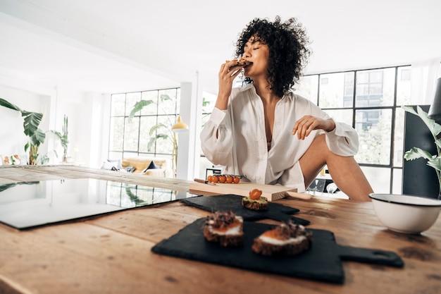 混血の女性がロフトアパートで朝食にアボカドトーストを食べる健康的なライフスタイルコピースペース