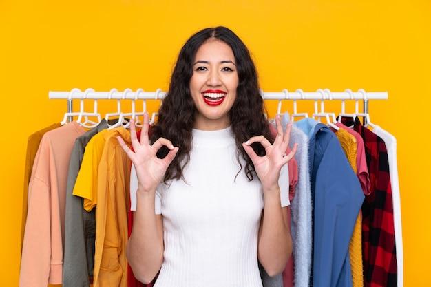 指でokサインを示す衣料品店で混血の女性