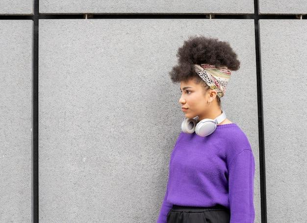 ヘッドフォンと携帯電話で、街で音楽を聴いている混血の女性