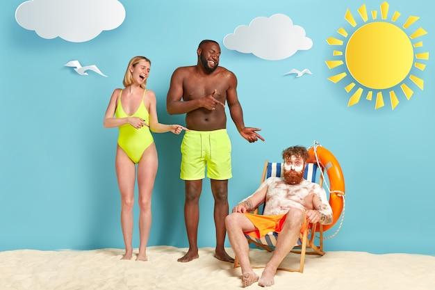 Uomo e donna di razza mista ridono di un simpatico amico ricoperto di crema bianca