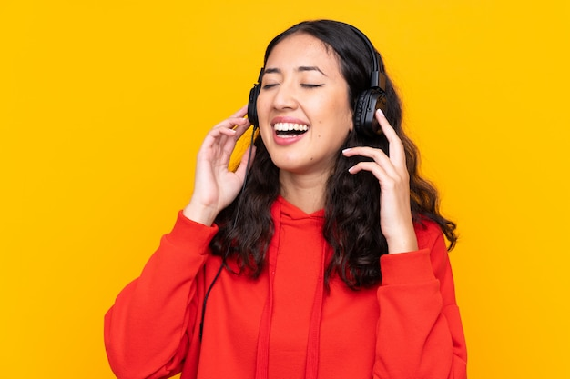 Mixed race woman wearing a red sweatshirt listening music and singing