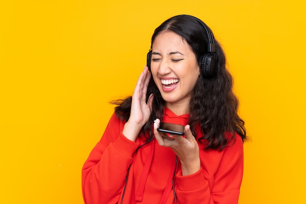 Mixed race woman wearing a red sweatshirt listening music with a mobile and singing