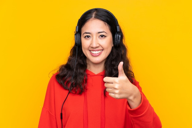 Mixed race woman wearing a red sweatshirt listening music and with thumb up