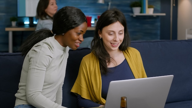 Mixed race women enjoying time spend together looking at movie on laptop while relaxing on couch. in background woman and man drinking beer, socializing late at night during relax party